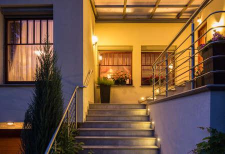 anochecer: Elegantes escaleras exteriores iluminados con barandilla de metal