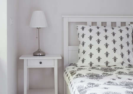 bedside: Stylish white bedside table with modern lamp Stock Photo