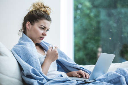 persona leyendo: Mujer enferma joven en la cama con el portátil Foto de archivo