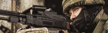 proving: Military young soldier is firing automatic weapon