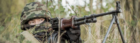sniper training: Armed young soldier on military maneuvers field Stock Photo