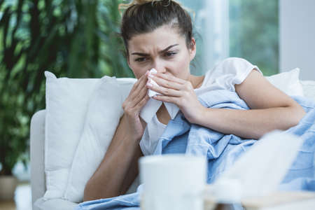 fever: Sick woman with runny nose lying in bed Stock Photo