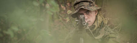proving: Hidden armed soldier is using automatic weapon Stock Photo