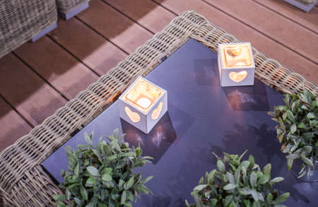 Tealights in stylish candleholders on glass table