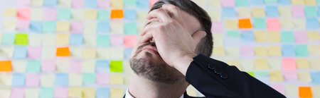 face work: Businessman after hard day at work,covering face with hand. Standing on sticky notes wall background, panorama Stock Photo