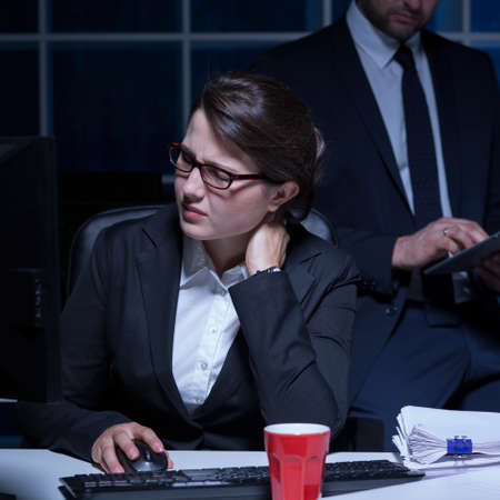 long hours: Businesswoman working long hours on urgent project Stock Photo
