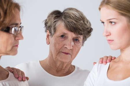 intergenerational: Image of sad senior and intergenerational family conflict