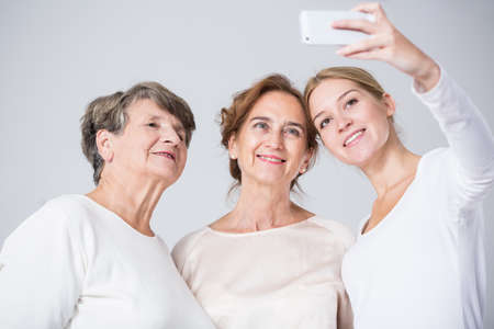 Image of happy family girls taking selfie