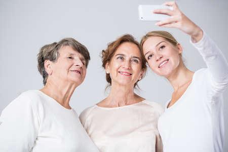 Image of happy family girls taking selfie