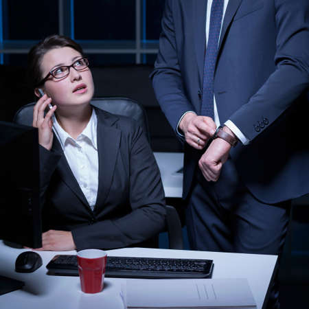 light duty: Young woman talking on phone at night in office