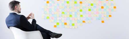 men in suit: Businessman sitting in front of sticky notes wall, panorama
