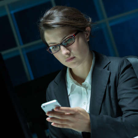 workaholic: Female workaholic is reading messages on phone