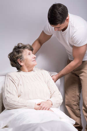 Young helpful man straightening older womans pillow