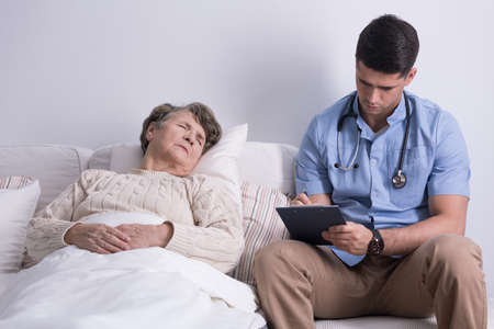 home visit: Older sick woman and her doctors home visit