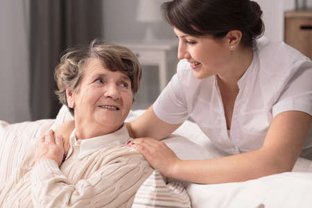 nursing assistant: Helpful young pretty woman and lovely older lady Stock Photo