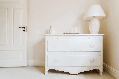 commode: White and stylish commode with a lamp Stock Photo