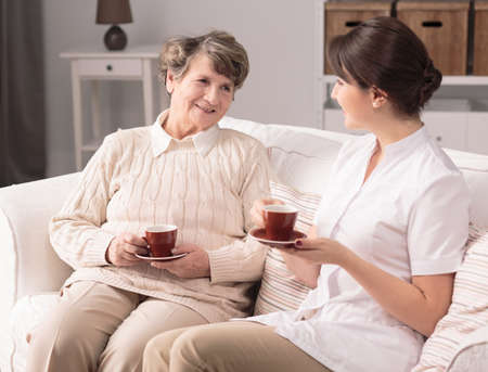 senility: Young happy caregiver having tea with older ward Stock Photo
