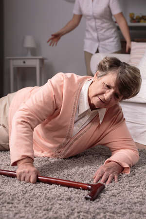 Senior disabled woman with walking stick fall on floor