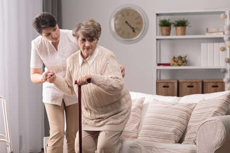 personas ayudando: cuidador joven que ayuda a señora mayor se pongan de pie