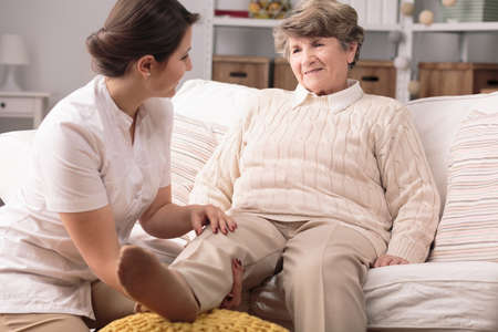 Older disabled woman with broken knee and her carer Stock Photo