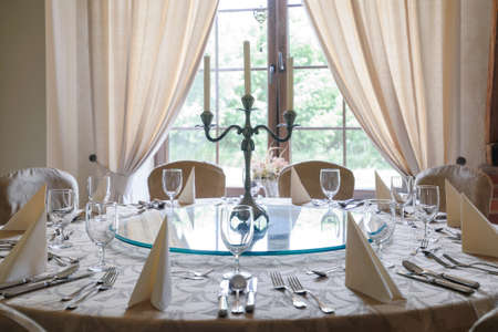 Round table with glasses, cutlery and candlestick in elegant luxurious restaurant