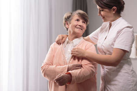Nice young carer giving the sweater to older lady Stock Photo