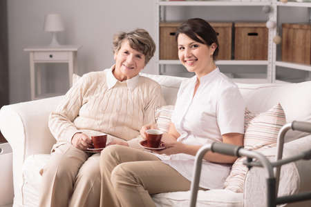 old time: Happy young female carer and senior woman spending time together Stock Photo