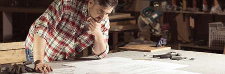 herramientas de trabajo: Carpenter, sosteniendo su barbilla, mirando en proyectos extiende sobre la mesa en su taller, panorama.