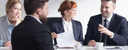 entrevista de trabajo: Hombre en el juego posterior de la visión de solicitar un trabajo en la corporación, y tres hombres de negocios sentado al lado de la mesa, panorama. Foto de archivo