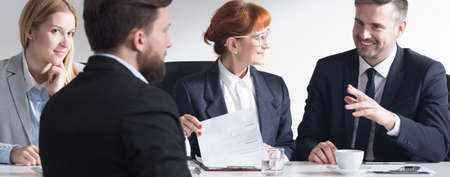 panorama: Man in suit back view applying for a job in corporation, and three businesspeople sitting beside table, panorama. Stock Photo