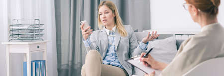 workaholic: Workaholic woman holding cellphone during session with psychologist, panorama. Stock Photo