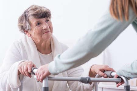 ancianos caminando: Mujer mayor con discapacidad caminar con la ayuda del cuidador Foto de archivo