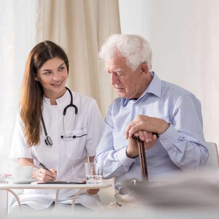 haushaltshilfe: Ältere Patienten zu lächelnden jungen Gemeindeschwester im Gespräch