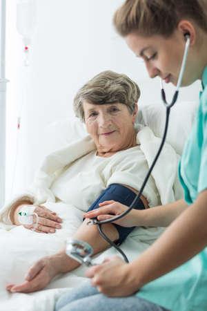 hipertension: mujer mayor con hipertensión y controla la presión arterial Foto de archivo