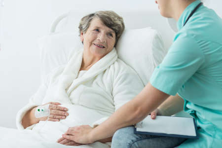 take a: Young nurse taking care of older patient Stock Photo