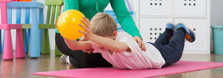 boy lady: Boy exercising with instructor on foam mattress, holding ball, panorama.