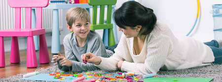 psychologist: Speech teacher and small boy during private home lesson, panorama.