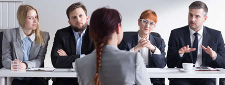 beside table: Woman applying for internship in corporation and four businesspeople sitting beside table, panorama. Stock Photo