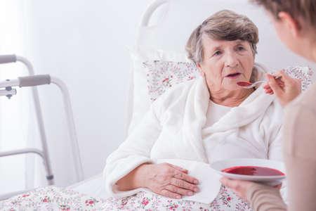 La donna più anziana malata di mangiare la cena con l'aiuto del caregiver Archivio Fotografico