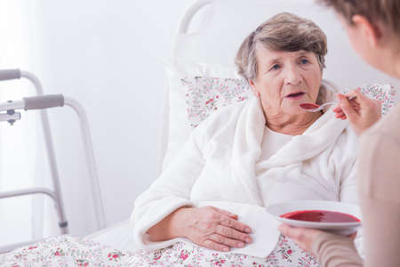 Plus ancien malade en train de dîner avec l'aide de soignants Banque d'images