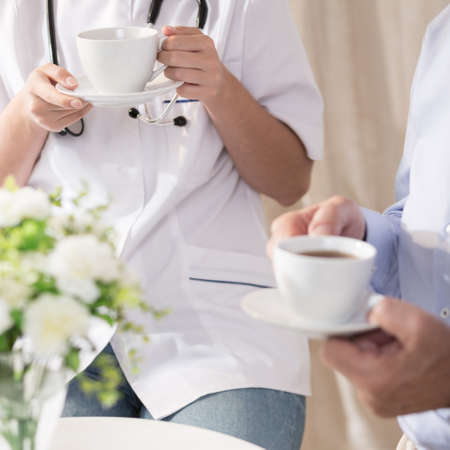consulta médica: Doctor y el consumo de café paciente durante la consulta médica Foto de archivo