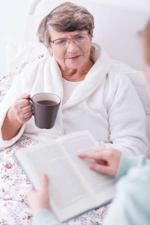 ward: Carer spending time with aged sick female ward Stock Photo