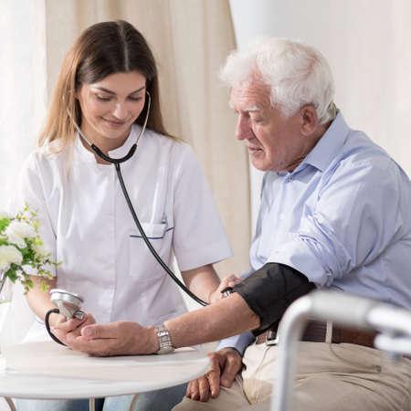 enfermera con paciente: Enfermera joven está tomando la sangre mayor de hombre Foto de archivo