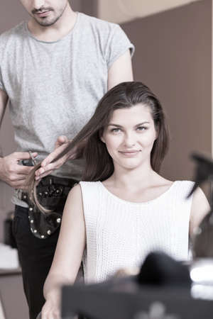 shorten: Young attractive lady having a haircut and hair styling Stock Photo