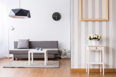 Stijlvolle woonkamer met grijze bank en een kleine salontafel. Licht inter met vloeren en decoratief behang. Stockfoto