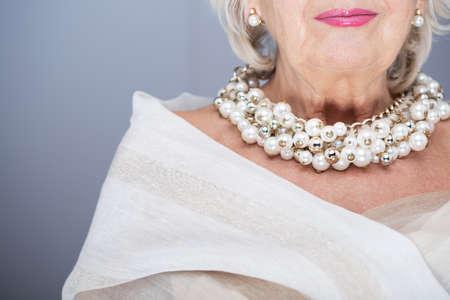 Rijke, senior vrouw, gekleed in elegante sjaal en kostbare parel sieraden Stockfoto