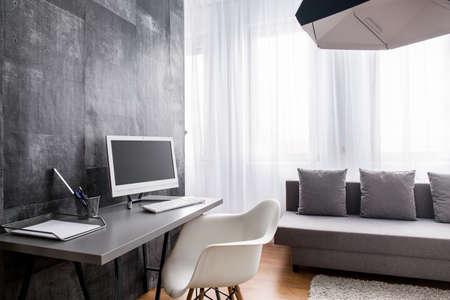Interieur met een bureau, stoel, bank en decoratieve cement behang.