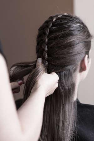 dutch girl: Hairdresser making a dutch braid - close up of hands