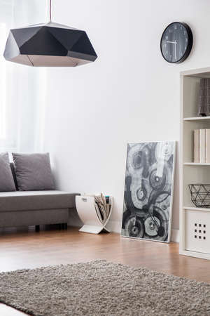 carpet and flooring: Room with carpet, flooring, sofa, bookcase and modern pendant lamp.
