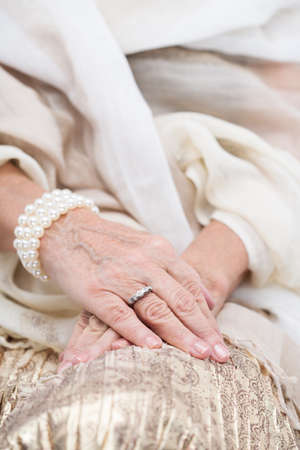 aristocracy: Close up of rich, senior womans hands. Woman with pearl bracelet and golden ring Stock Photo